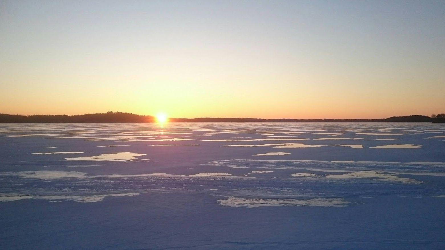 Aurinko laskee jäätyneen Simpele-järven takana.