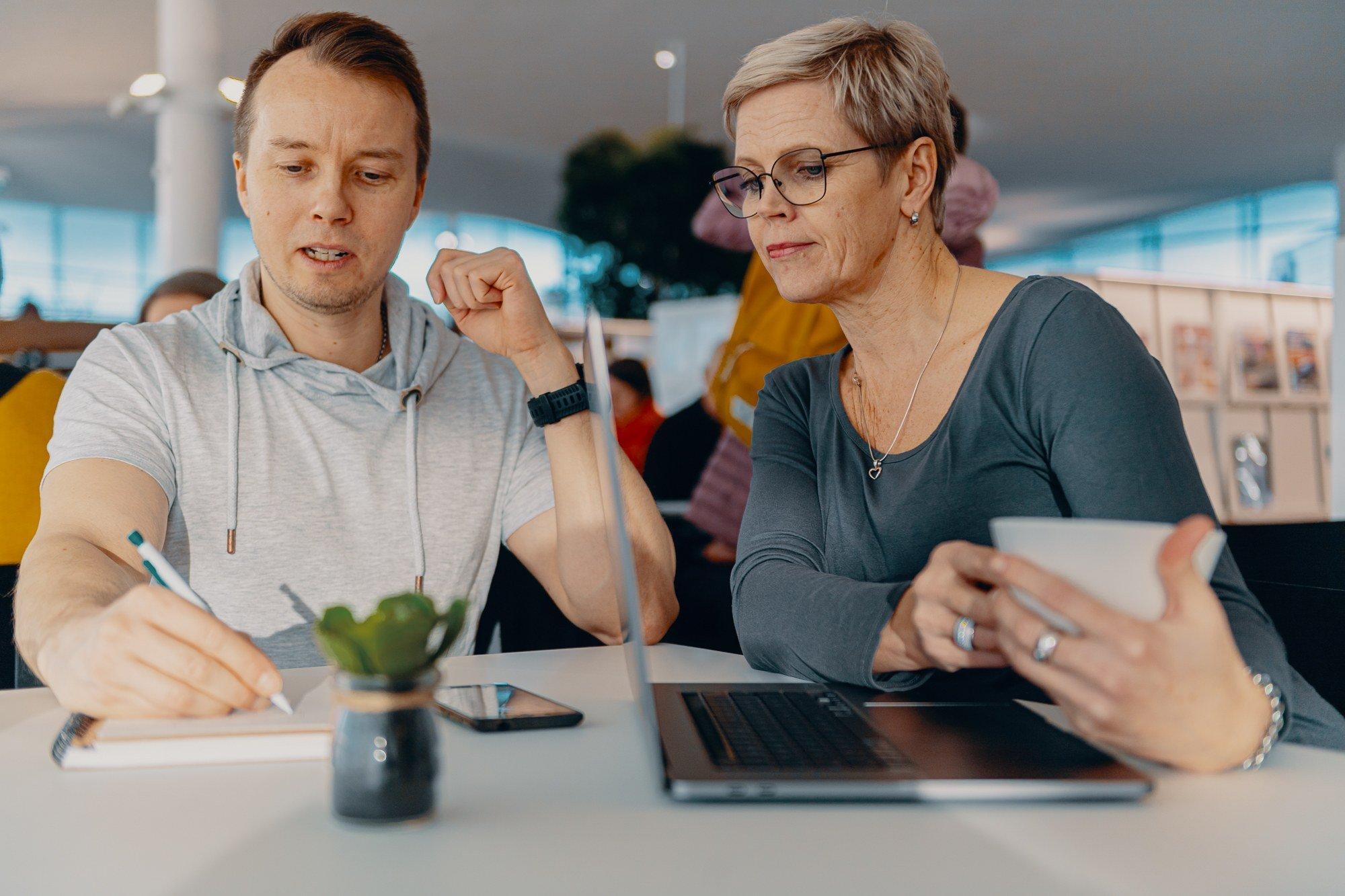 Mies kirjoittaa muistivihkoon. Nainen katsoo vieressä. Pöydällä on kannettava tietokone.