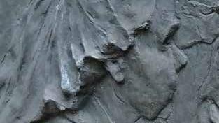 Kiveen veistetyt ihmisen kasvot.