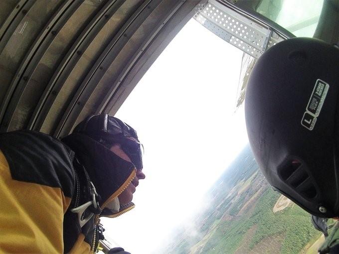 Lentäjä ilmassa. Ikkunasta näkyy maisemaa ilmasta käsin.