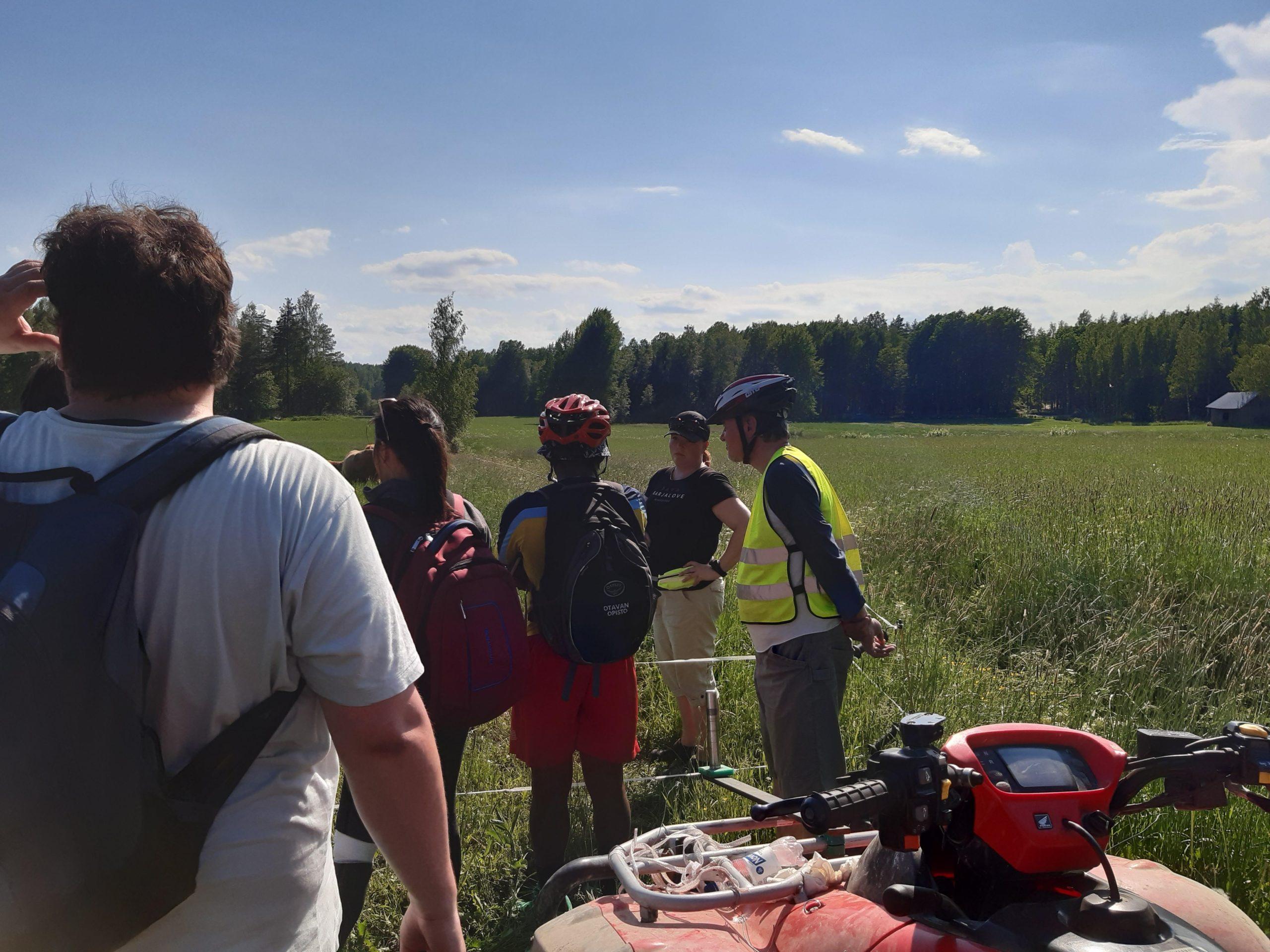 Pyöräilijät pitävät taukoa pellon laidassa kauniina kesäpäivänä.