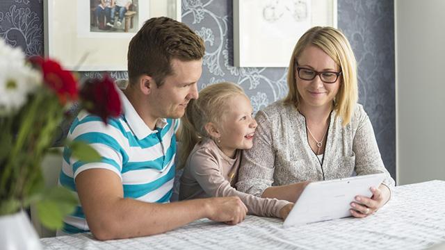 Kolmehenkinen perhe istuu pöydän ääressä ja katsoo kannettavaa tietokonetta.